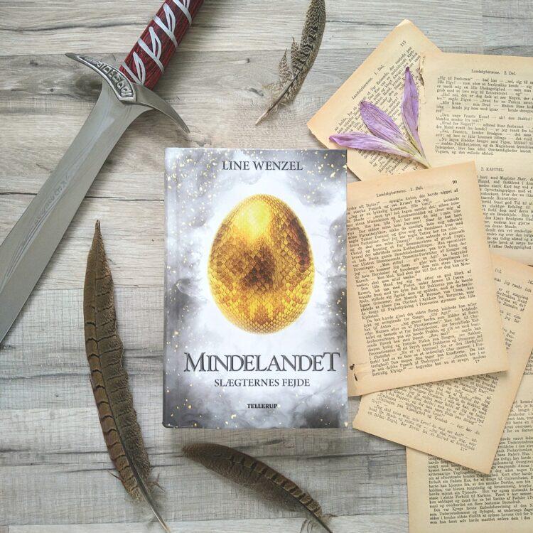 Bogen Mindelandet 3: Slægternes fejde ligger på gråligt trægulv. Til højre ligger spredte bogsider med en lyselilla blomst. Omkring bogen ligger fjer spredt ud. I top venstre hjørne ligger et sværd.