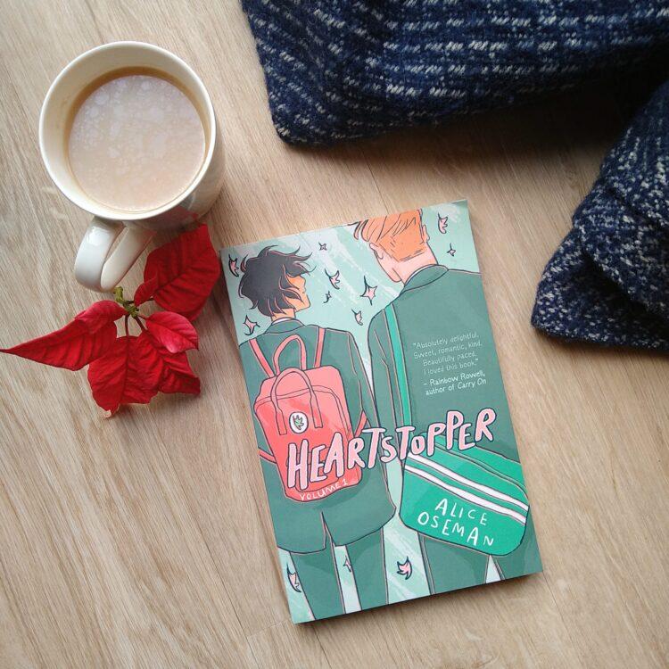 Bogen Heartstopper af Alice Oseman ligger ved et mørkeblåt tæppe og en kop te med mælk i ved siden af en rød blomst