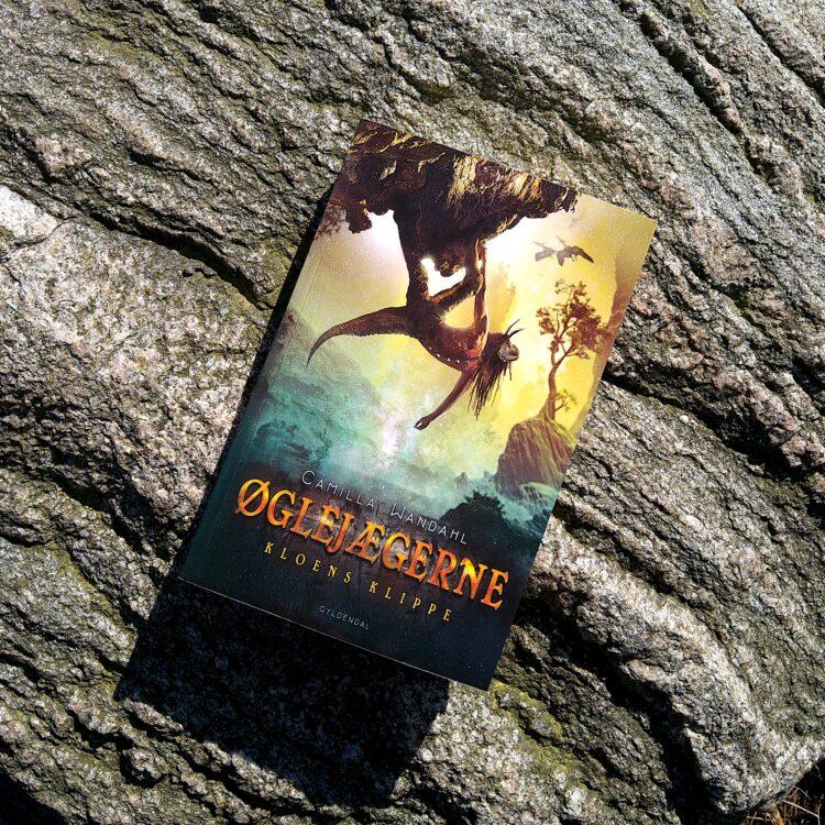 Bogen Øglejægerne Kloens Klippe ligger på en baggrund af klippe sten i solskin
