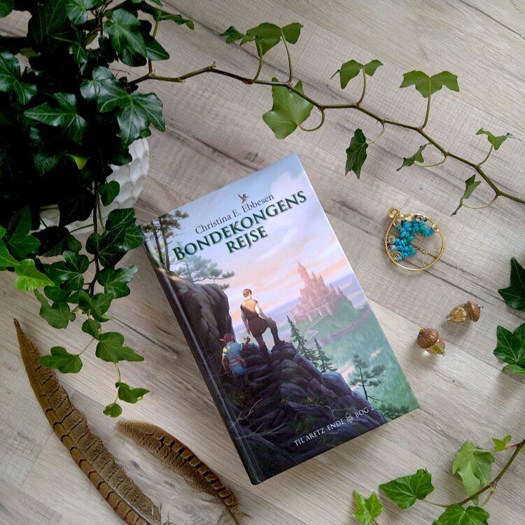 Bogen Bondekongens rejse sammen med en efeu plante et par fjer og smykke agern