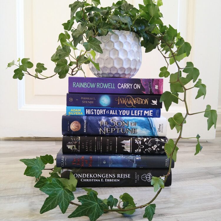 Bogstak med fantasy og Young Adult bøger med en grøn plante ovenpå