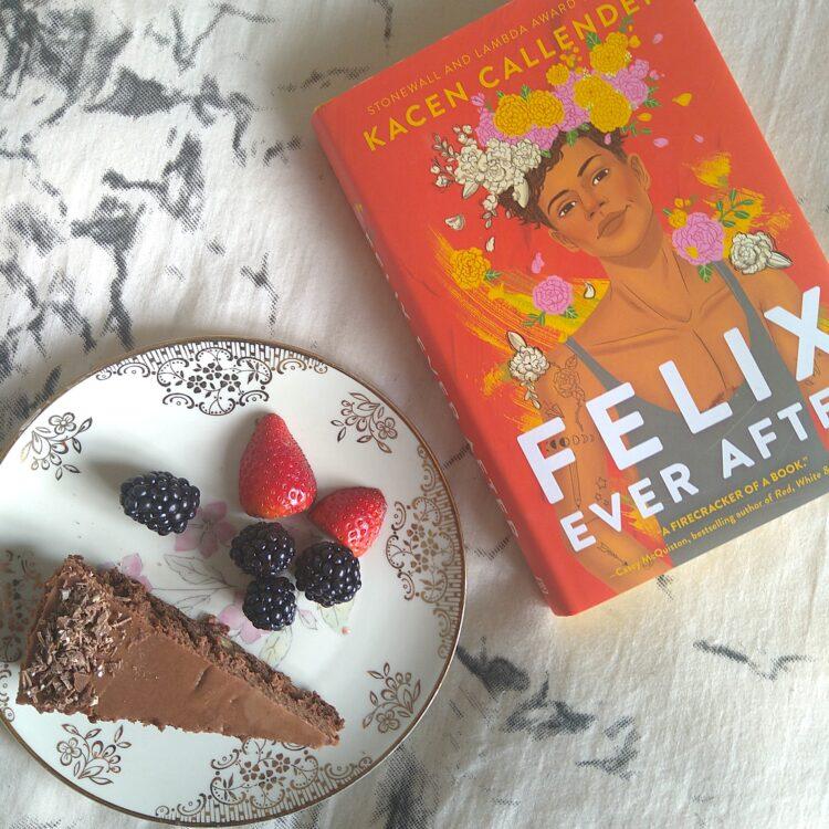 Bogen Felix Ever After på en baggrund af sort og hvidt sengetæppe ved siden af en tallerken med chokoladekage og jordbær og brombær