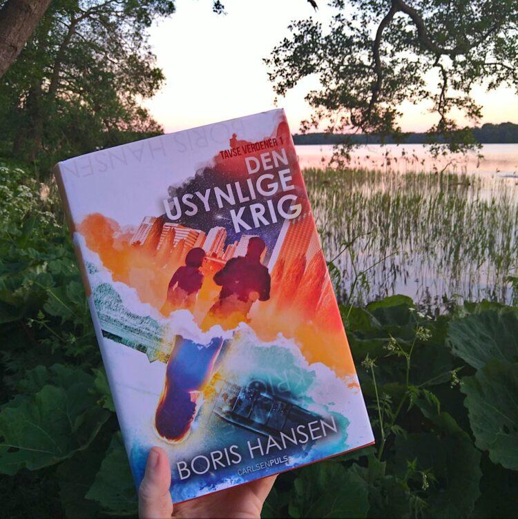 Romanen Den usynlige krig som er bind et i serien Tavse verdener er i forgrunden, mens en sø med solnedgang udgør baggrunden for billedet