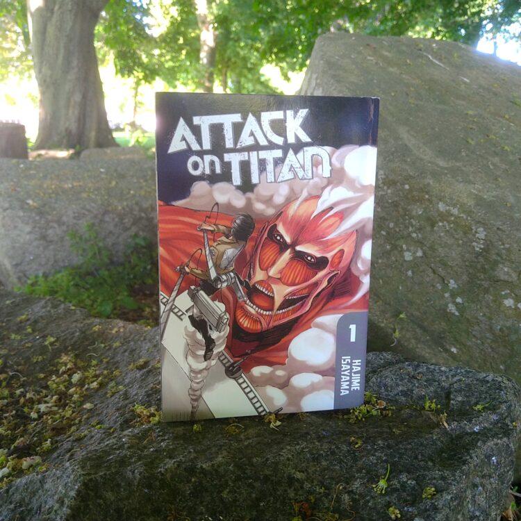 manga volume 1 af attack on titan stående på murbrokker i en park