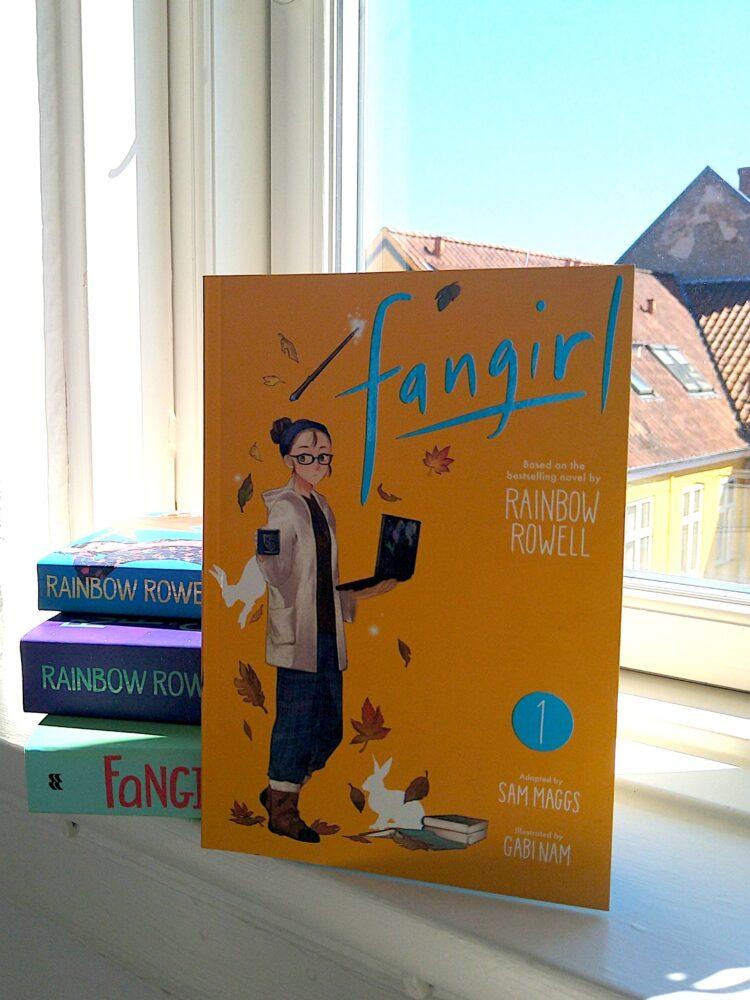 Manga eller Graphic Novel udgaven af Fangirl af Rainbow Rowell sammen med de tre andre bøger i samme univers, står i et vindueskarm på en sommerdag