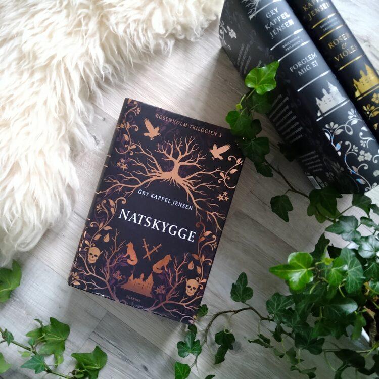 Bogen Natskygge af Gry Kappel Jensen ligger sammen med de to andre bøger i Rosenholm-trilogien, en grøn plante og et hvidt fåreskin dekorerer.